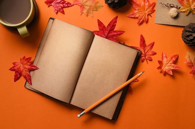 오렌지 배경에 빈티지 책, 커피 컵, 가을 단풍나무 잎.