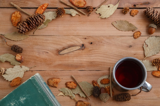 Vintage book and drink in retro mug on wooden background. top view