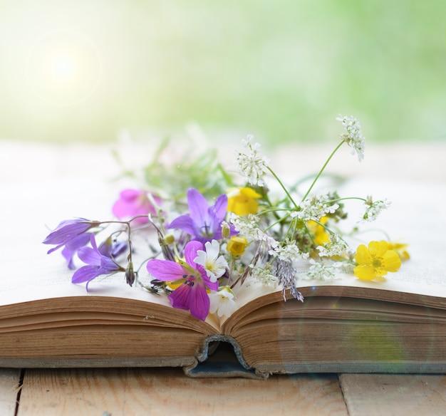 초원 꽃 향수 배경의 꽃다발과 빈티지 책