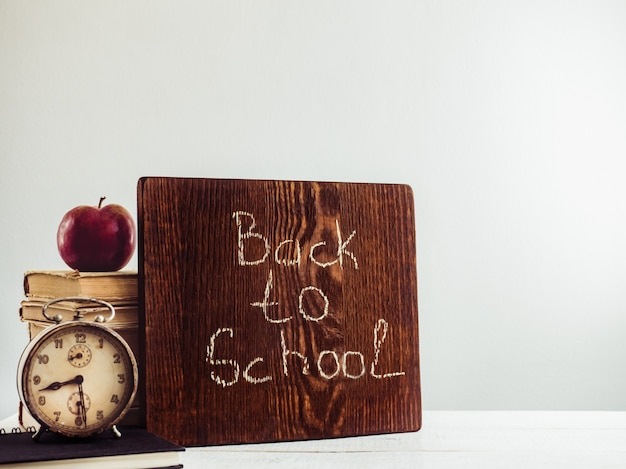 Vintage books, old clock, pencils, red apple and blackboard