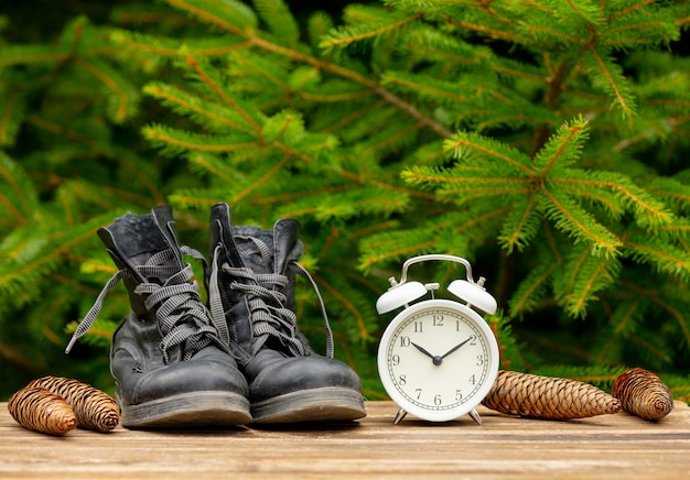 Vintage boots and alarm clock on wooden table with spruce branches on background