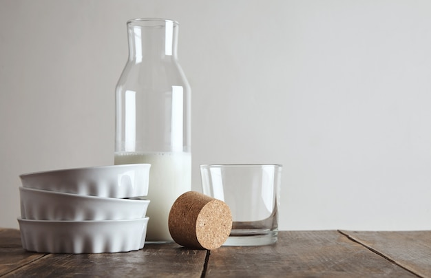 Tappo di sughero aperto bottiglia vintage con latte sulla tavola di legno invecchiato vicino vetro trasparente di whisky rox e tre piatti in ceramica, isolati su bianco