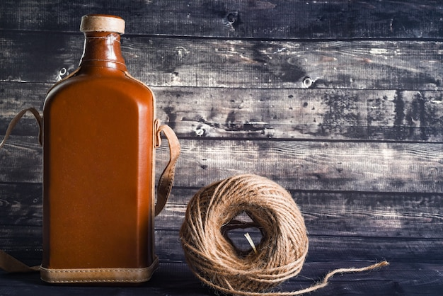 Vintage bottle of whiskey and a ball of thread for the interior on a dark wood background