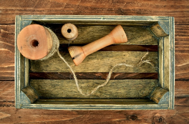 Vintage box with bobbins, reels, spools, threads and lace. small box of tools in wooden workshop