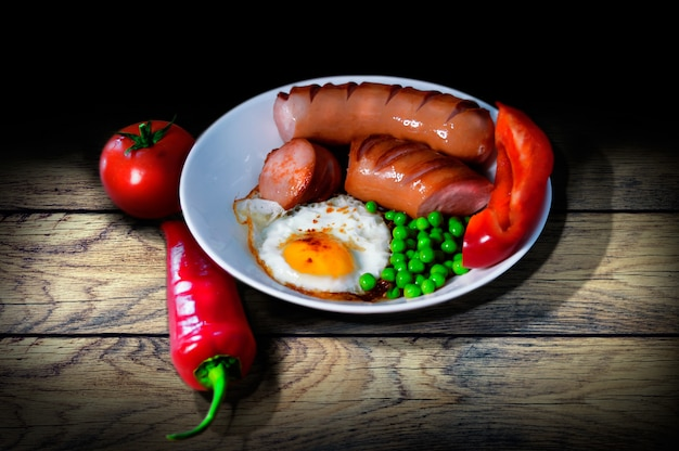 Vintage breakfast on wooden table of fried peas and peas sausages pepper and tomato