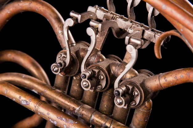 Vintage bronze pipes, valve, key mechanical elements french horn on black isolated background.
