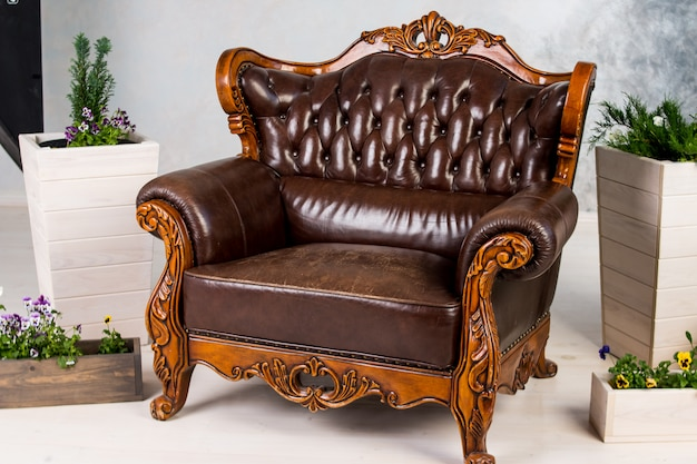 Винтажное коричневое кресло и большие коробки с садовыми цветами.