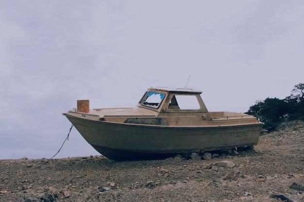 Винтажная коричневая лодка на скалистой и песчаной поверхности