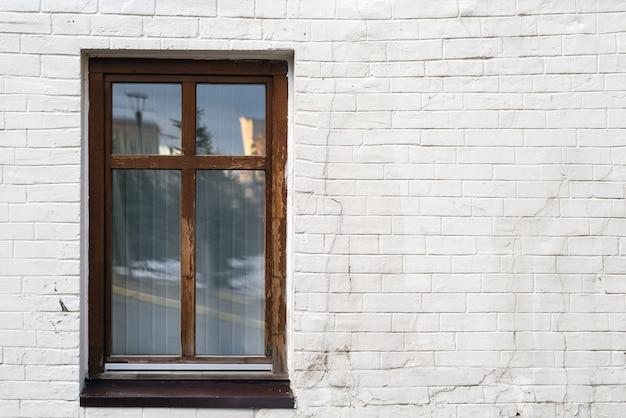 Винтажное коричневое высокое окно на белой кирпичной стене с космосом экземпляра, космосом для текста.