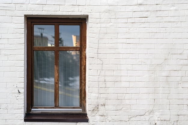 Vintage brown high window on white brick wall with copy space, space for text.