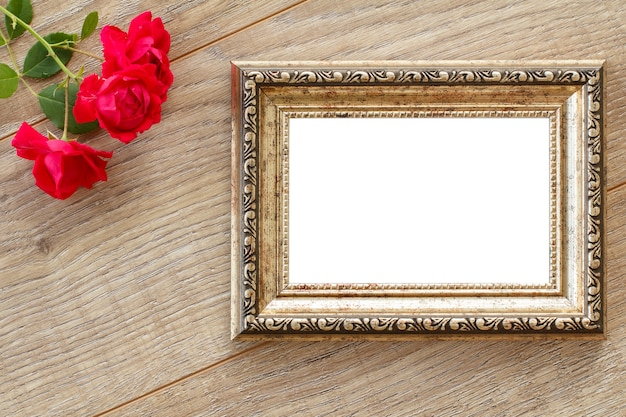 Vintage brown photo frame with copy space and red rose flowers on wooden boards. top view.