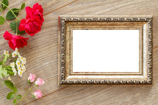 Vintage brown photo frame with copy space, red rose and white chamomile flowers on wooden boards. top view.