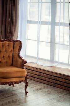 미니멀리즘 스타일의 객실 내부에 빈티지 갈색 소파. 파노라마 창