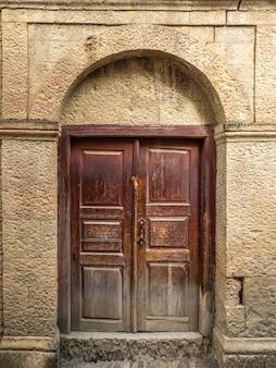 山の本物の村のヴィンテージ茶色の木製のドア。