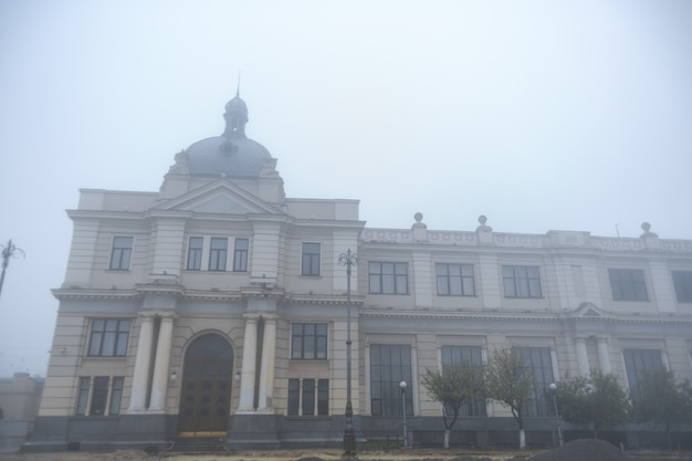 Vintage building of railway station in fog weather.