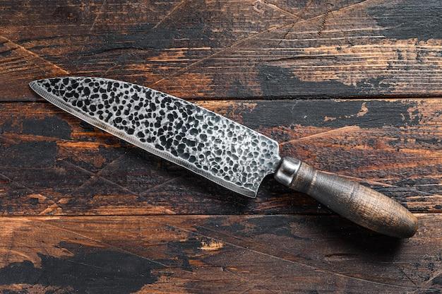 ヴィンテージ肉屋の肉ナイフ。暗い木製の背景