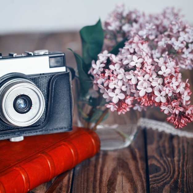 Vintage camera and bouquet of lilac spring flowers on wooden bac