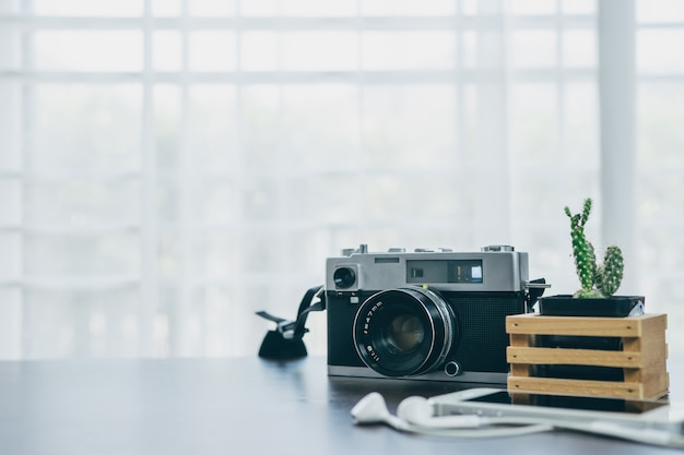 Vintage camera and cactus placed on a wooden table with a white background