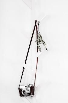 Vintage camera hanging on a white coat rack