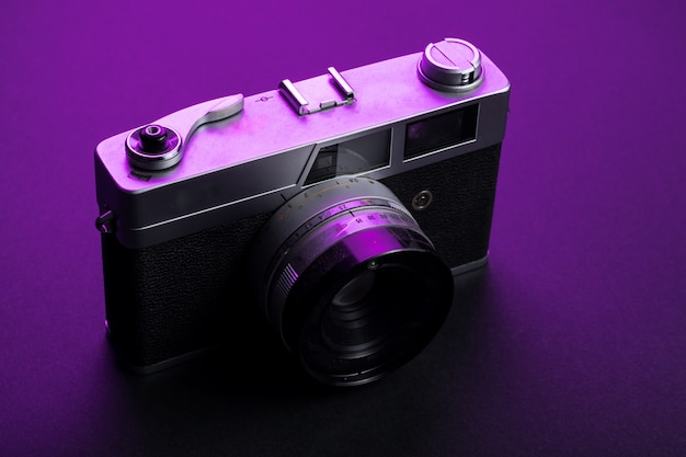 Vintage camera isolate on black and purple light