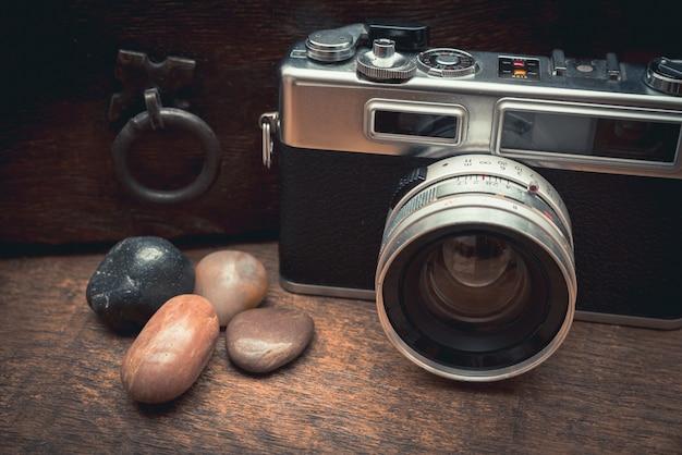 Macchina fotografica vintage e pietre naturali su un tavolo di legno vicino al vecchio baule