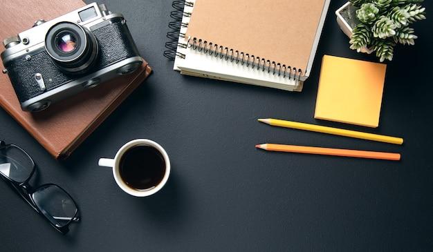 一杯のコーヒーとメモ帳のビンテージカメラ