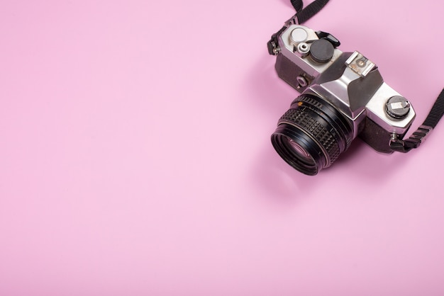 Vintage camera on pink background