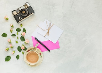 Vintage camera; pink rose; green leaves; envelope; paper; pen and coffee cup on concrete background