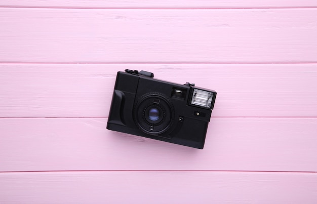 Vintage camera on pink wooden background.
