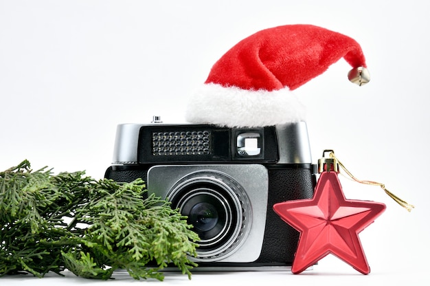 孤立した白い背景の上のクリスマスツリーとおもちゃに囲まれたヴィンテージカメラ