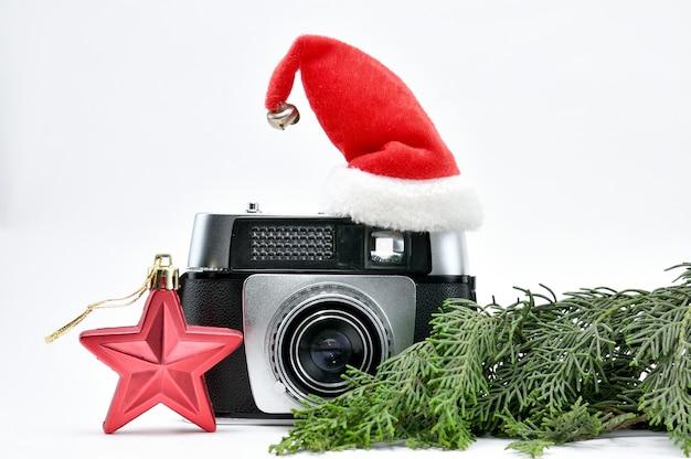 孤立した白いスペースにクリスマスツリーとおもちゃに囲まれたヴィンテージカメラ
