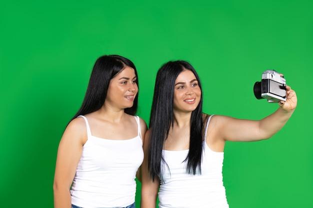 Старинные фотоаппараты сестры-близнецы улыбаются и фотографируют