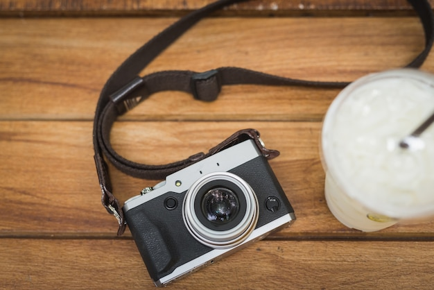木製のテーブルに氷のコーヒーとヴィンテージカメラ