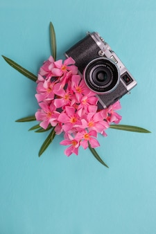 Vintage camera with pink flora on blue background.