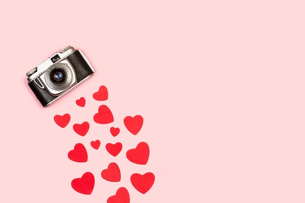 A vintage camera with red hearts on a pink background