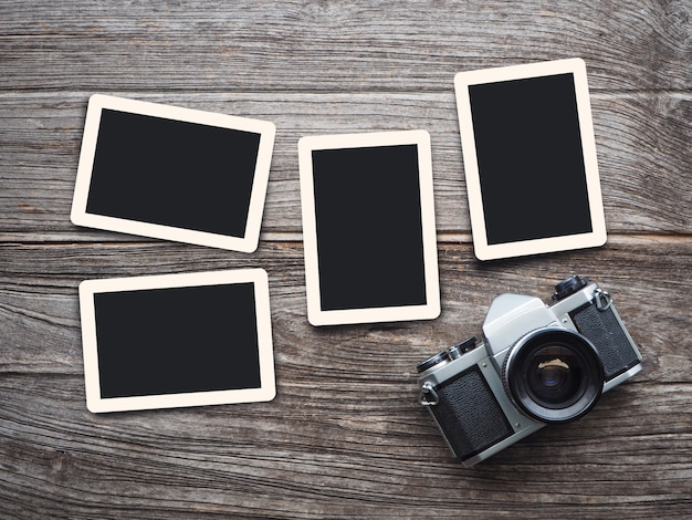Vintage camera on wooden background with blank photo frames