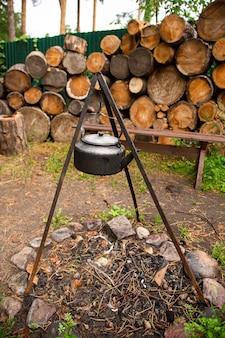 Старинный кемпинг чайник над открытым огнем в летнем лесу