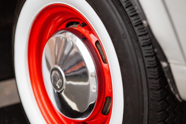 Vintage car wheel, painted red, the concept of the history of the development of cars.