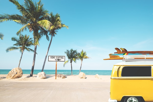 Vintage car with surfboard on roof on tropical beach in summer. beach sign for gone surfing.