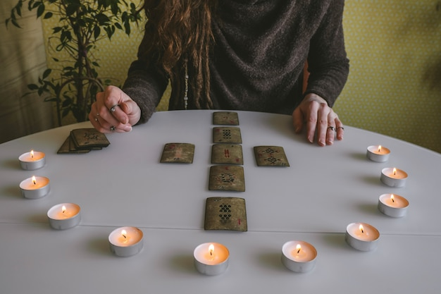 Vintage cards with runes symbols and circle of candles on a white table