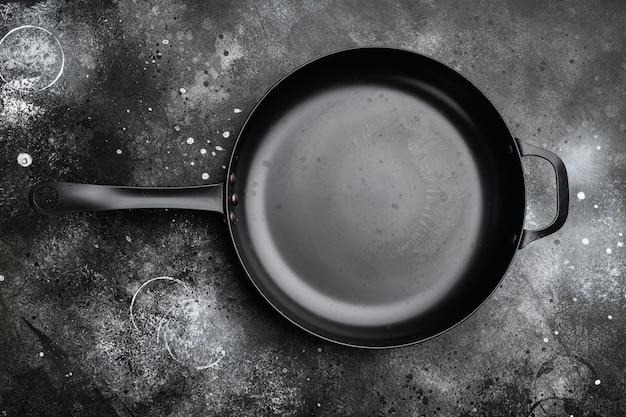 Винтажная чугунная сковорода с копией пространства для текста или еды с копией пространства для текста или еды, плоская планировка, вид сверху, на черном фоне темного каменного стола