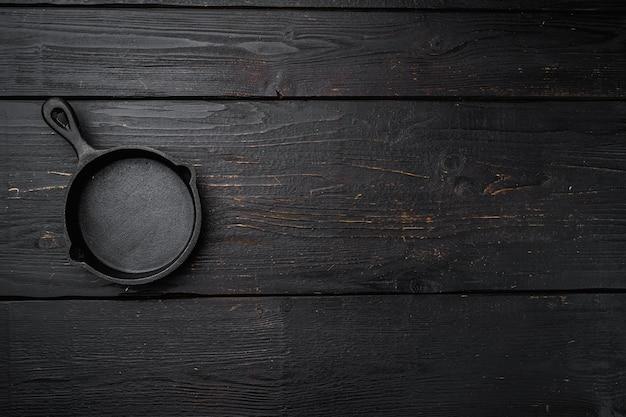 Винтажная чугунная сковорода с копией пространства для текста или еды с копией пространства для текста или еды, плоская планировка, вид сверху, на черном фоне деревянного стола