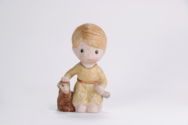 Vintage ceramic doll of boy and sheep for interior decoration white background.