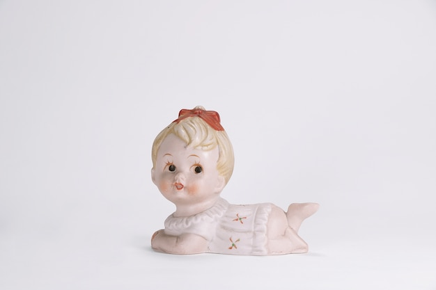 Vintage ceramic doll of cute baby girl for interior decoration white background.