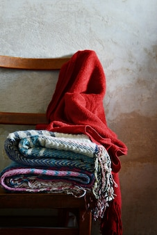 A vintage chair with a stack of warm woolen blankets near the concrete wall.