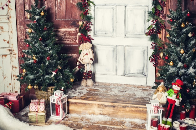 Старинное рождественское украшение входной двери с подарками и огнями