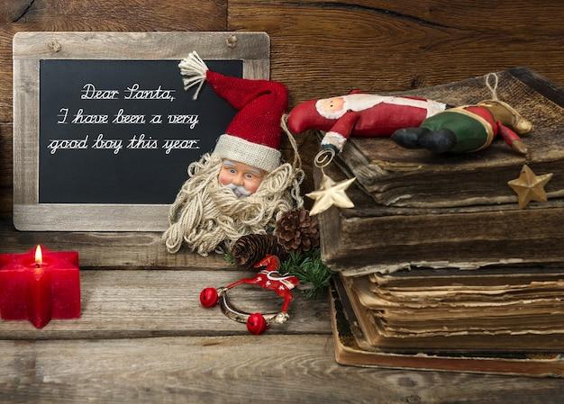 골동품 장난감과 나무 배경에 빨간 촛불 빈티지 크리스마스 장식. 샘플 텍스트와 칠판 친애하는 산타. 어두운 디자인, 선택적 초점