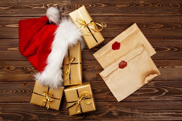 Старинное рождественское поздравительное письмо и упакованные подарочные коробки на деревянном фоне