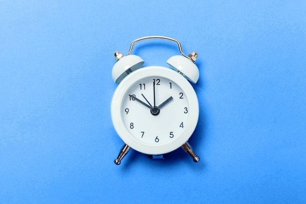 Vintage classic alarm clock isolated on colored in trendy color of year 2020 classic blue background. bright macro color . flat lay top view copyspace.