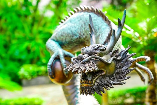 녹색 정원에 아시아 중국 용의 빈티지 클래식 동상이 있습니다.
